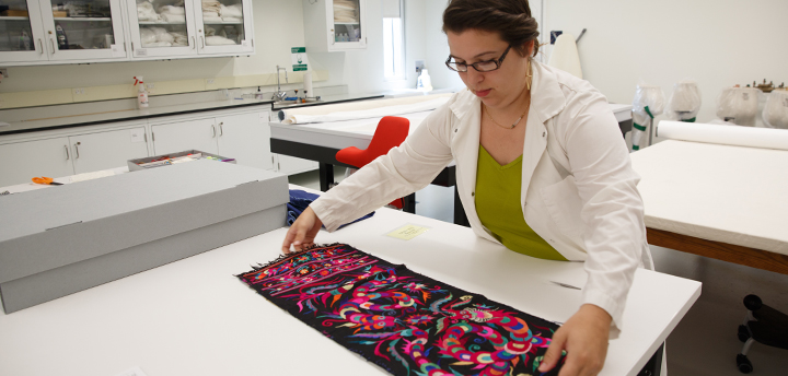A museum conservator works on a textile