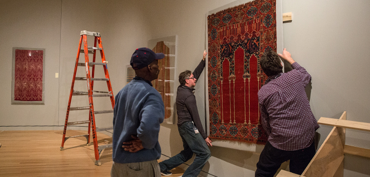Museum staff hang a prayer rug in the galleries