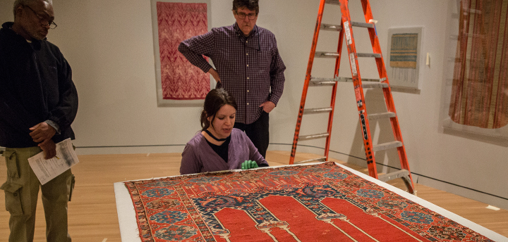 Museum staff prepare to hang a textile in the galleries