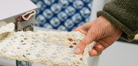 A visitor handles a fabric sample in Textiles 101 gallery
