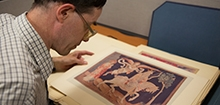 A visitor examines a book in the library's collection