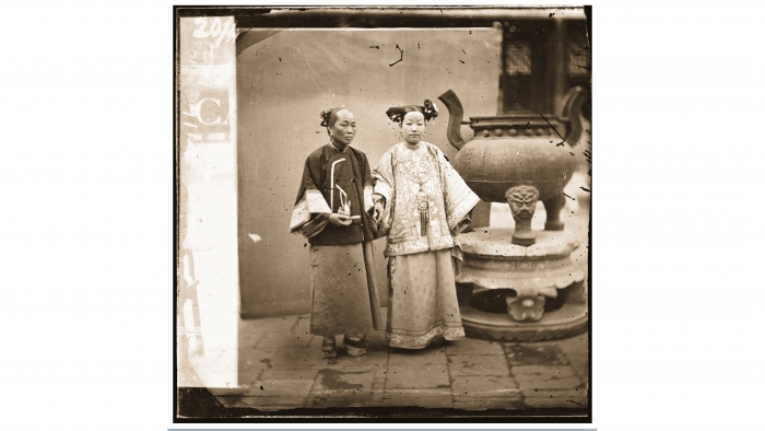 Two women standing near an incense-burner
