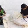 Appliqué artisans stitching reverse appliqué motifs