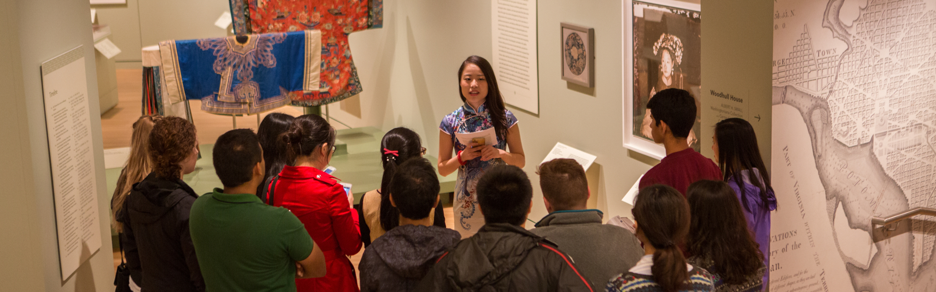 Woman talking to group of students in front of textiles