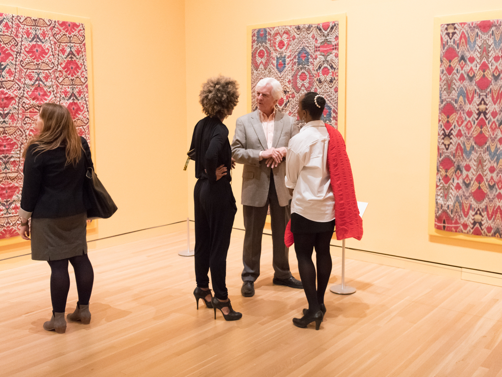Four visitors look at colorful artworks in gallery
