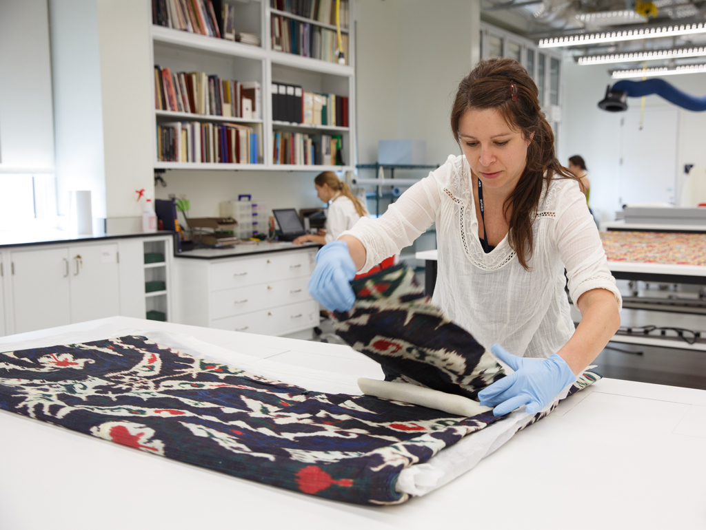 Woman unfolds textile in lab