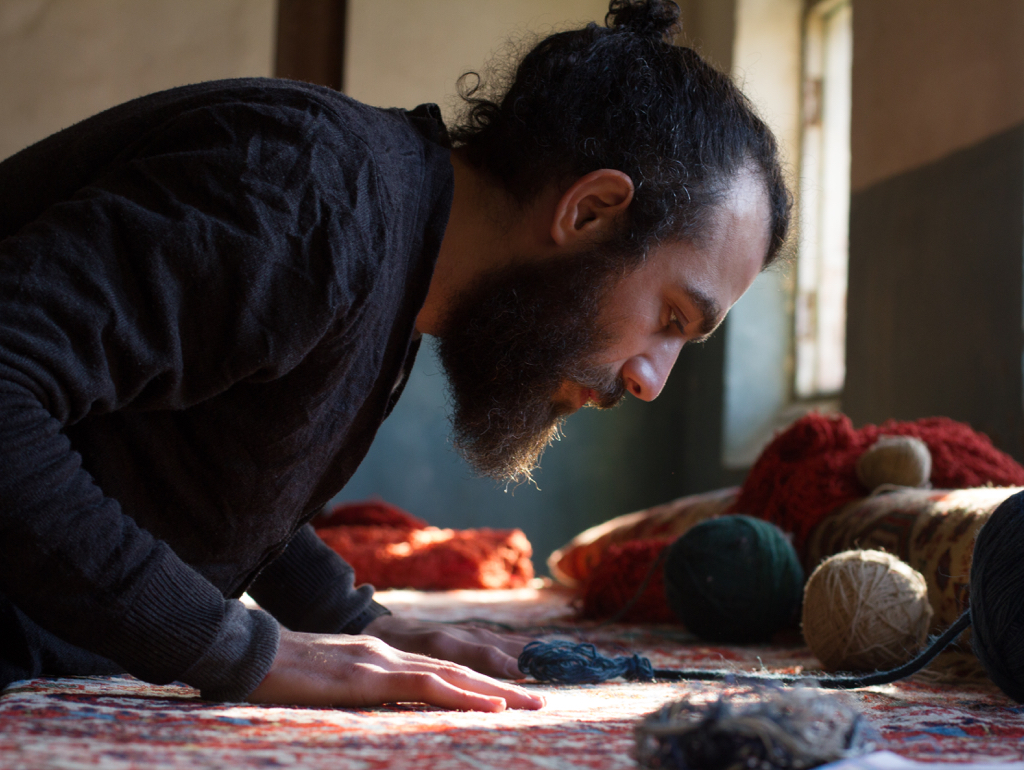 Artist with hands on carpet