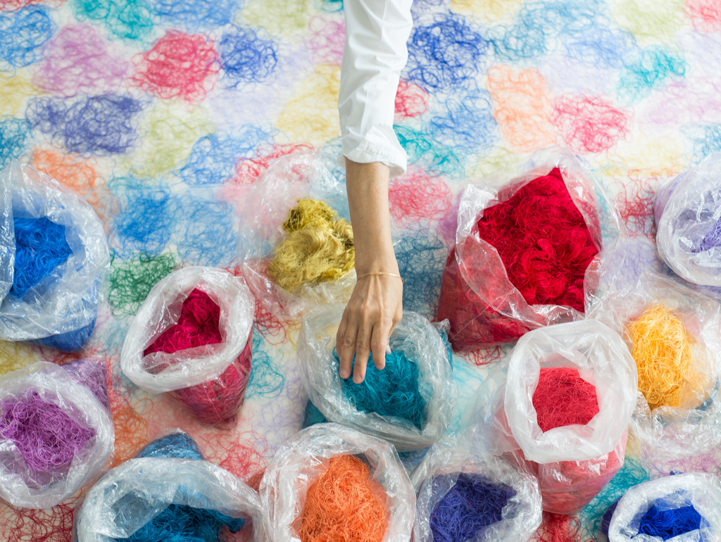 Hand reaching into bags of colorful thread