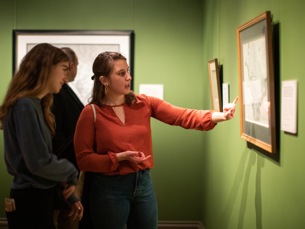 Two college students look at print in gallery