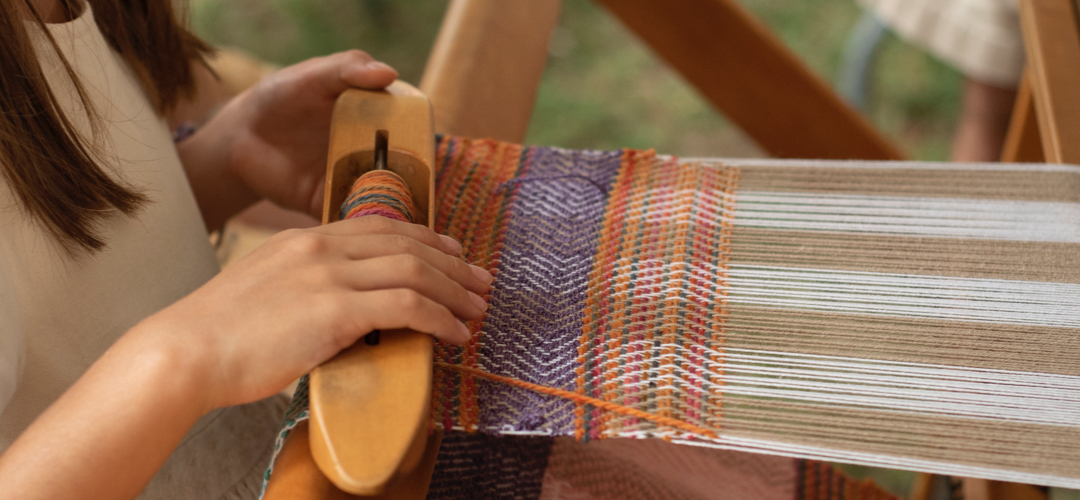 Girl weaving on a loom