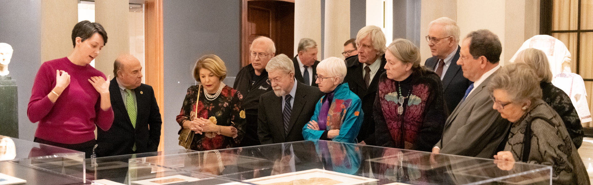 Large group of adults looking at materials in glass case