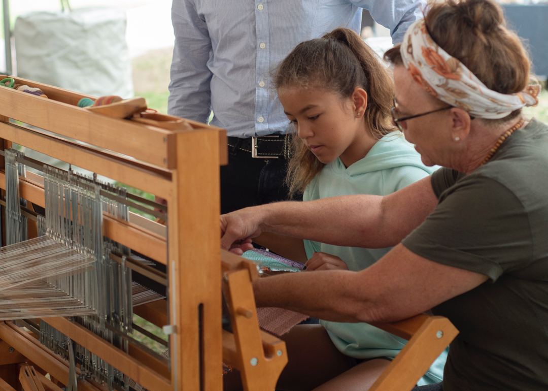 Child weaving on loom