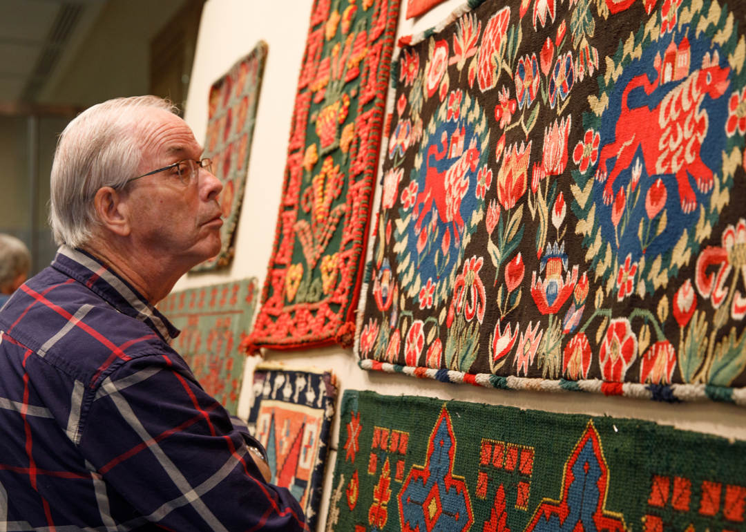 Man looking at colorful weavings