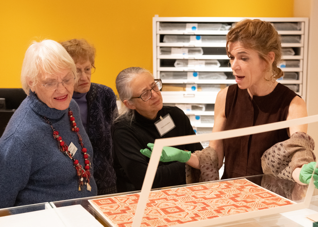 Women looking at textiles under glass