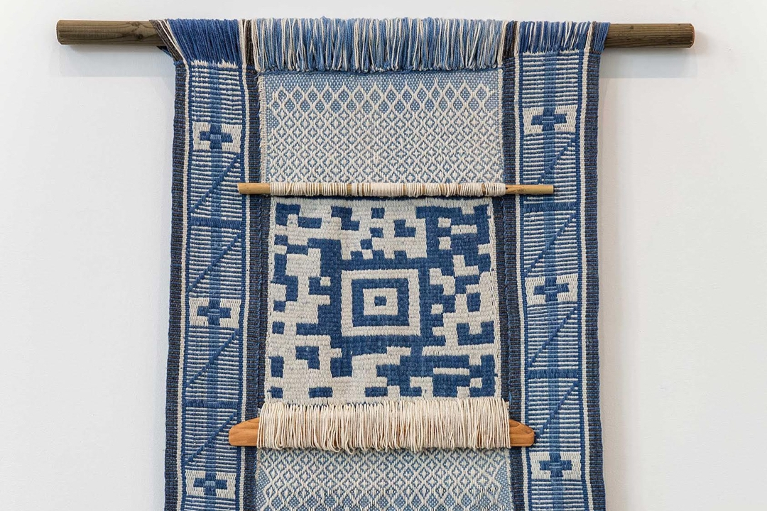 Blue and white textile with a woven QR code design
