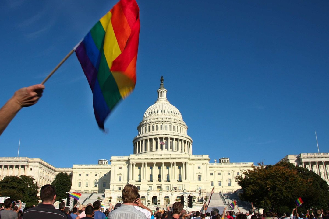 Hand waving Pride flag in front of the Capitol