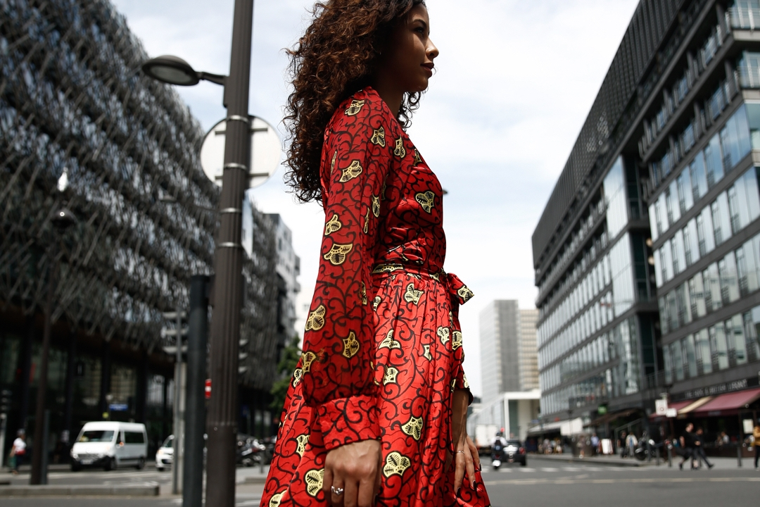 Woman in wax print dress walking in a city
