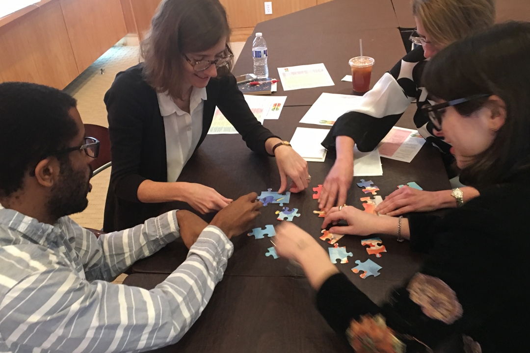 Four people work on an activity at a table