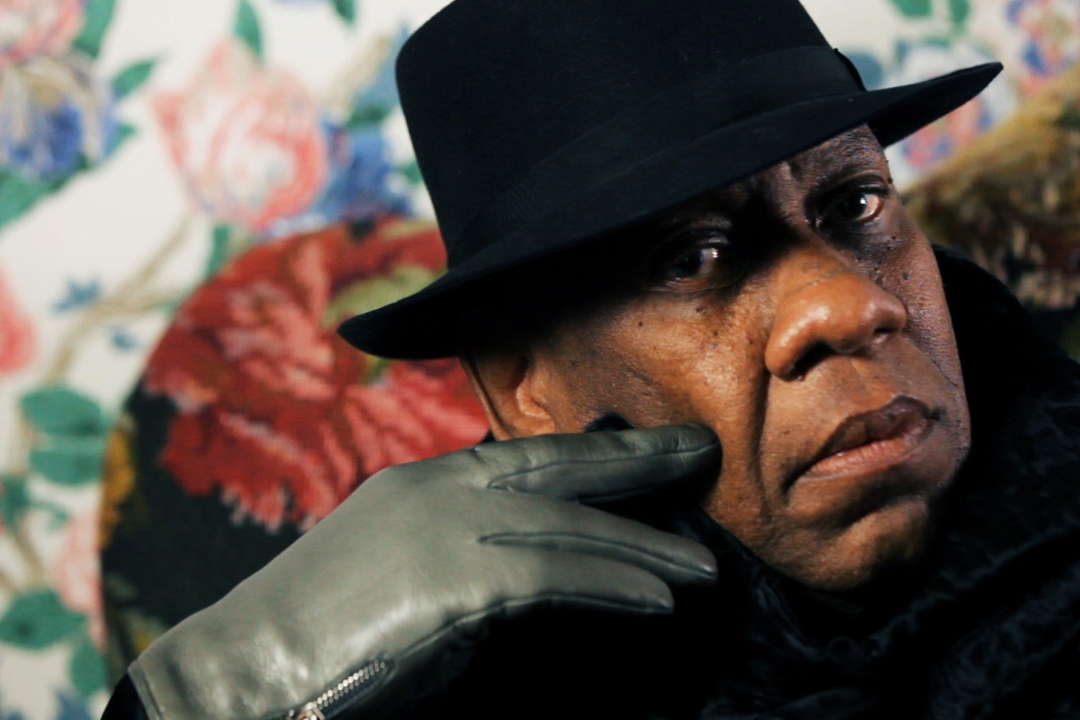 Andre wearing black fedora and gloves
