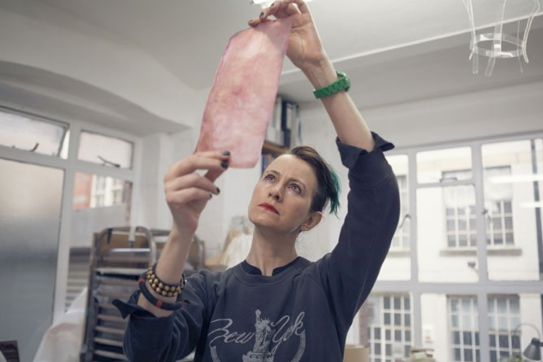 Woman holding a piece of fabric up to the light