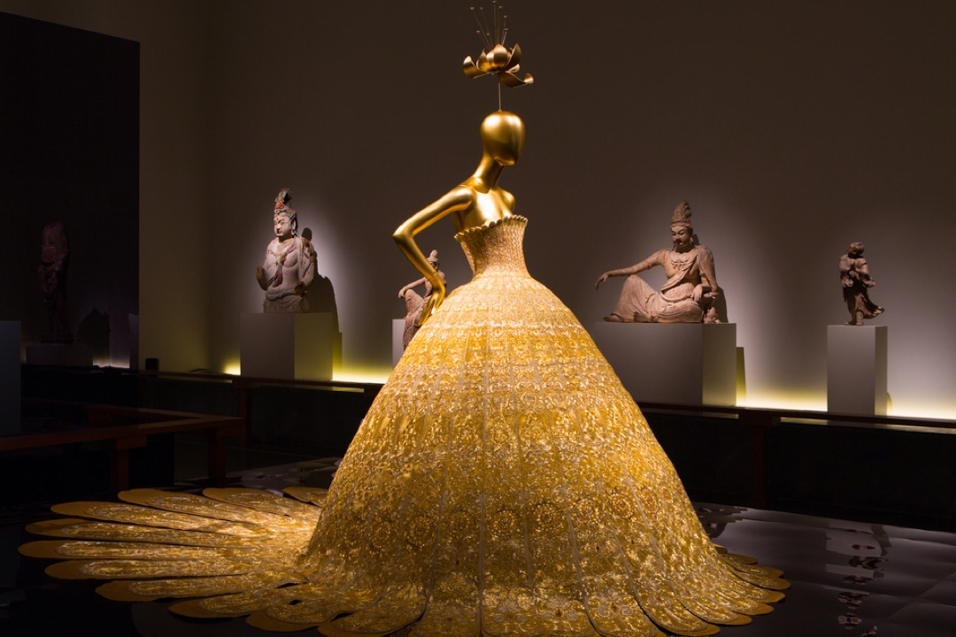A mannequin wearing an elaborate gold dress
