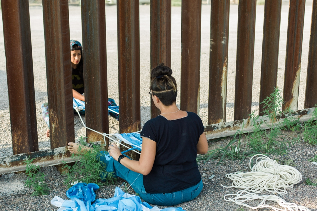 Two people sit on either slide of a slatted border wall, facing each other and working together on a textile.