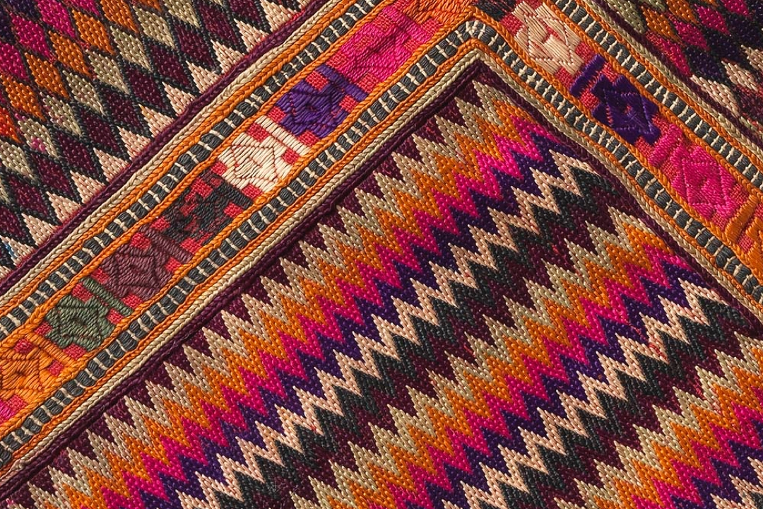 Detail of a pink, purple, orange and white textile with geometric patterns