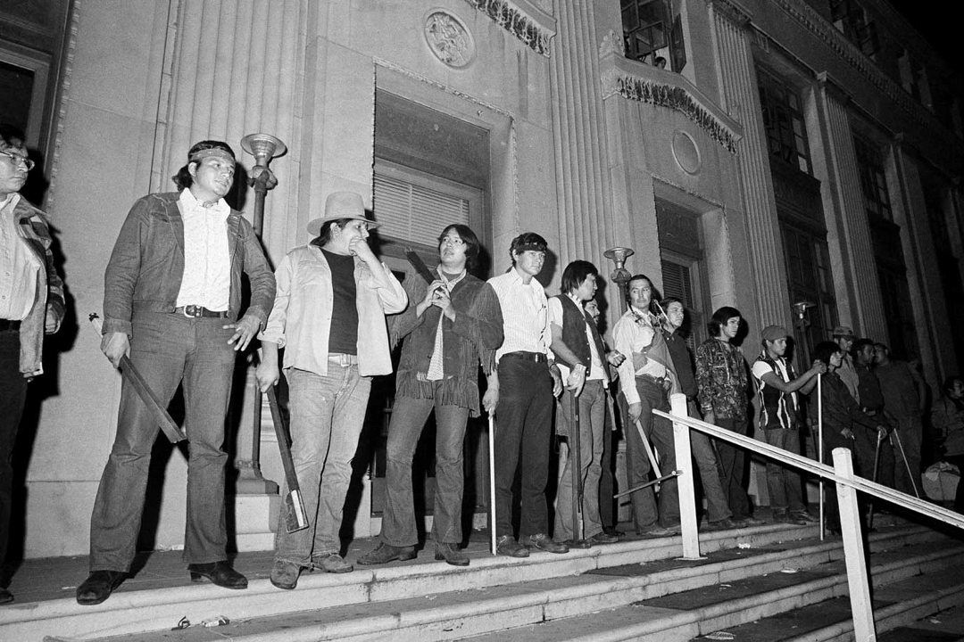 Group of American Indian activists gathered in front of a government building.