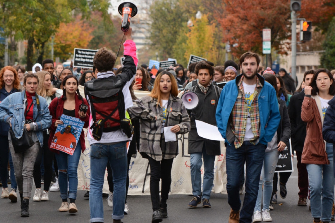 Diverse group of students walking down a street in a protest