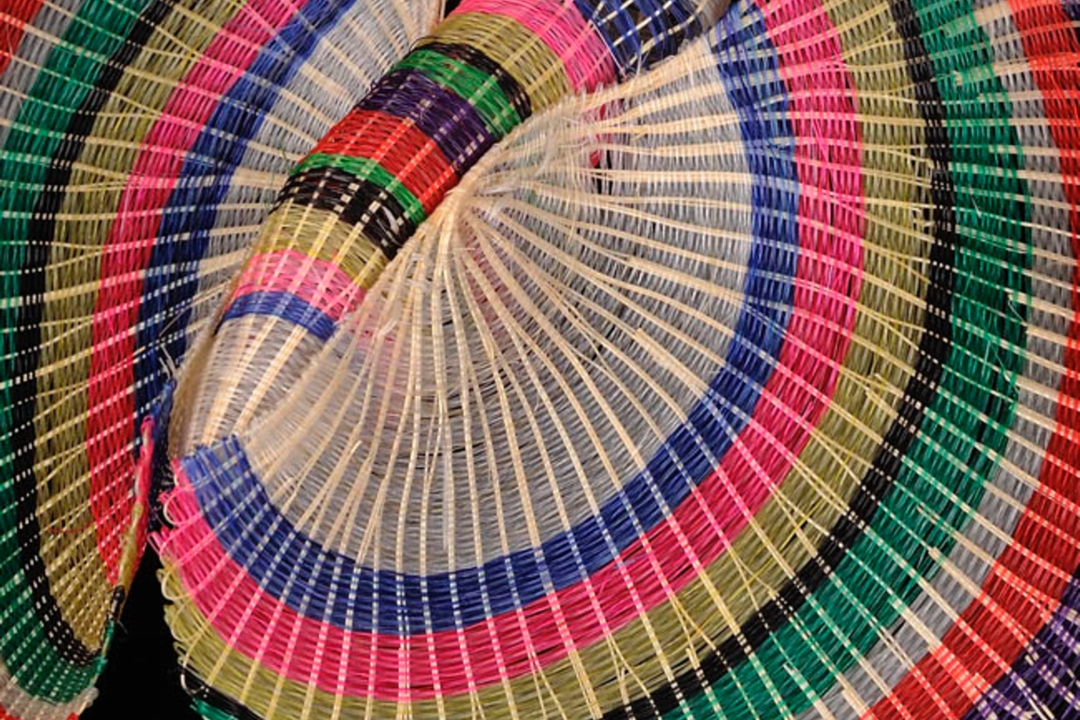 Basket with bright, striped colors of pink, blue, yellow, green and white.