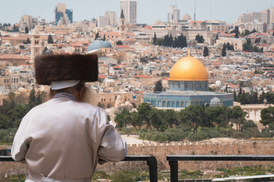 """A man wearing a """"shtreimel"""" hat looking out over the city of Jerusalem with the Dome of the Rock clearly visible."""