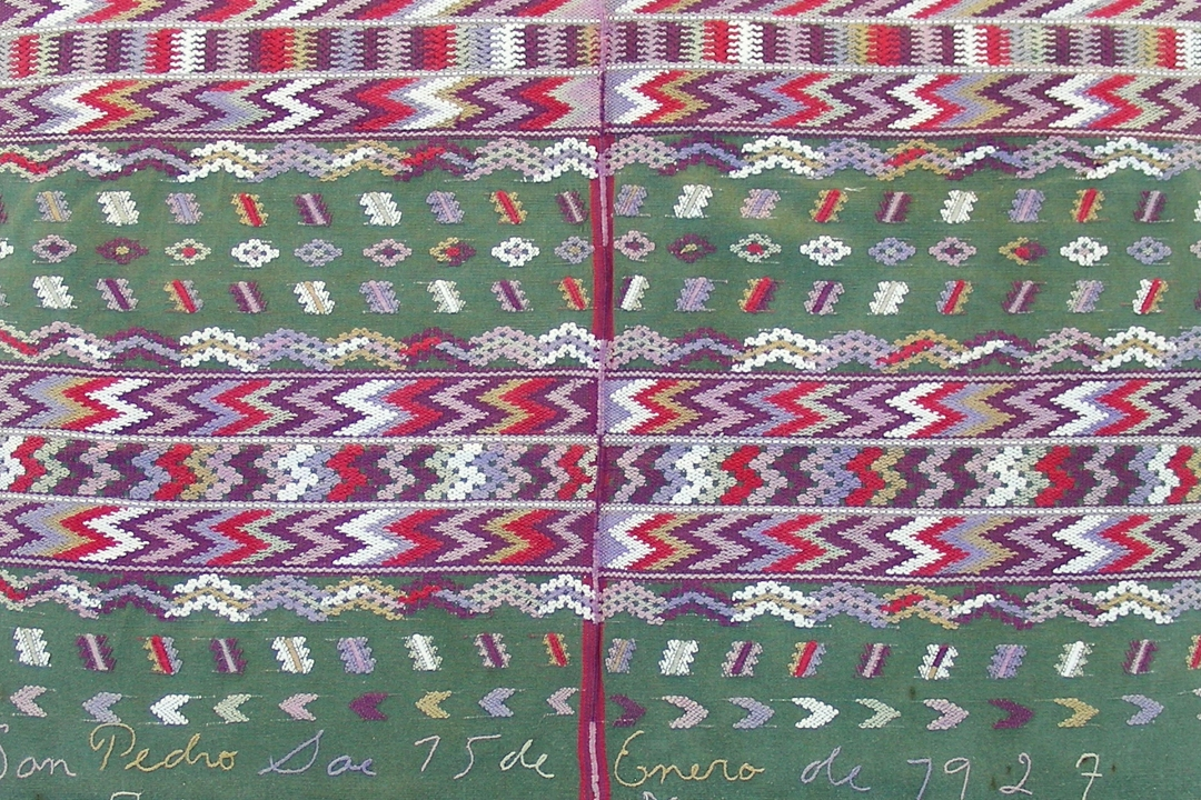 Green textile with red, purple, blue and white geometric patterns and embroidered writing towards the bottom