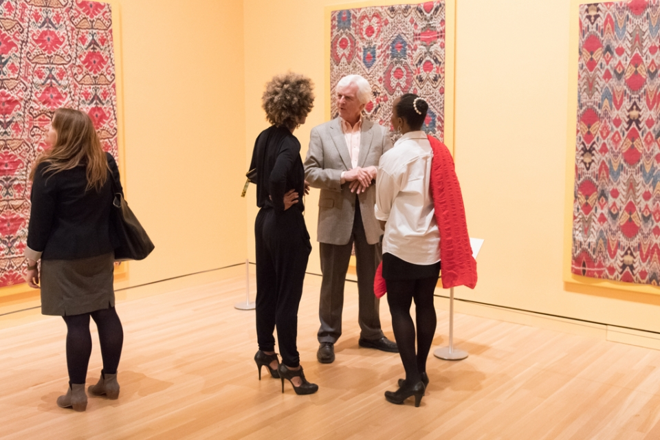 Four visitors look at colorful textiles in gallery