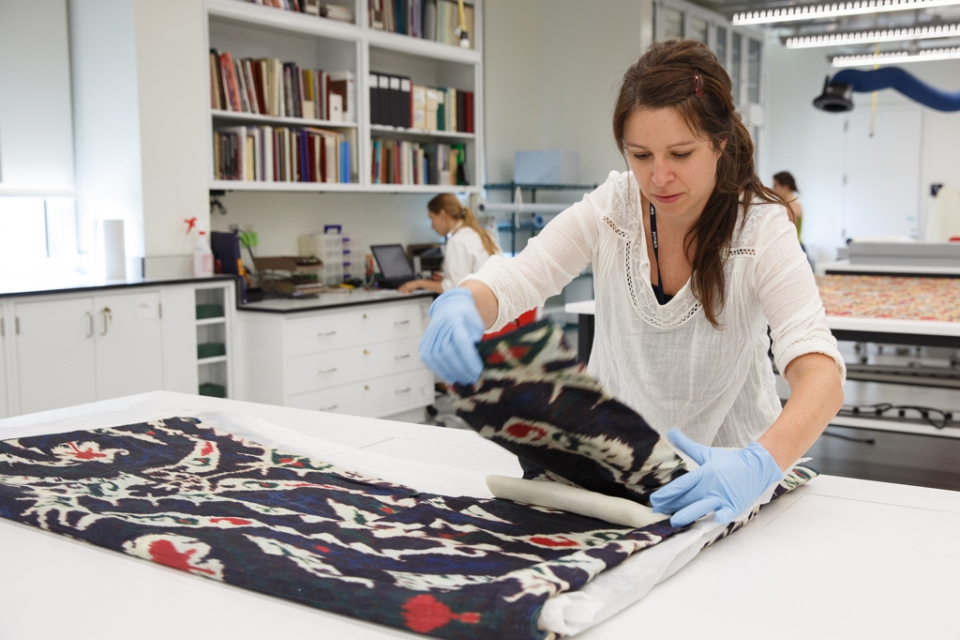 Woman folding textile in lab
