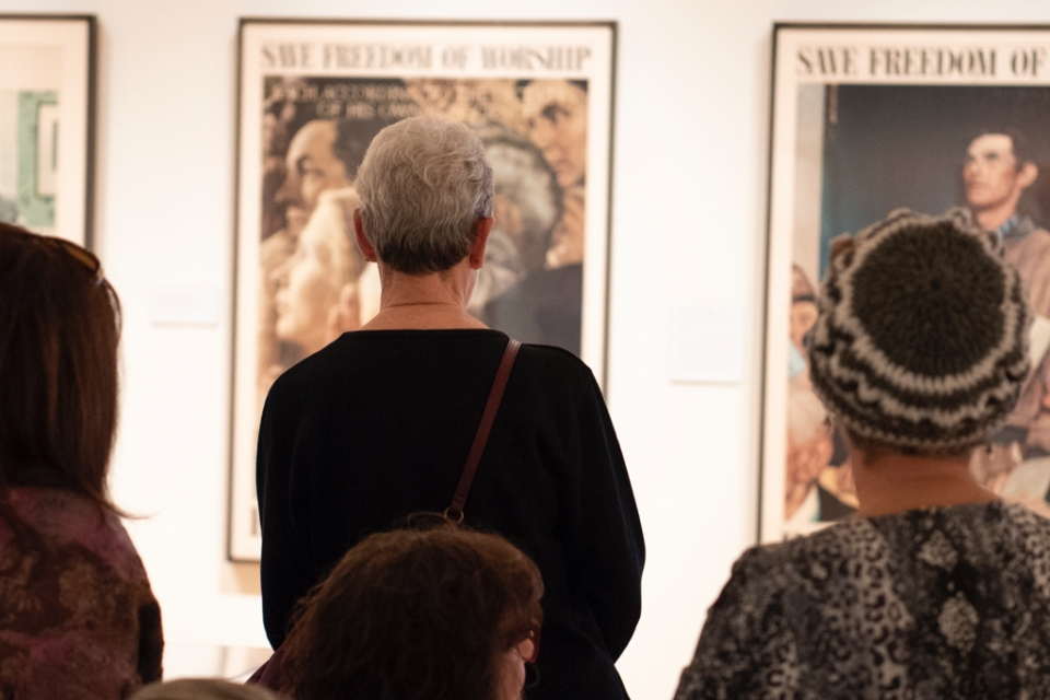 Visitors look at Rockwell posters
