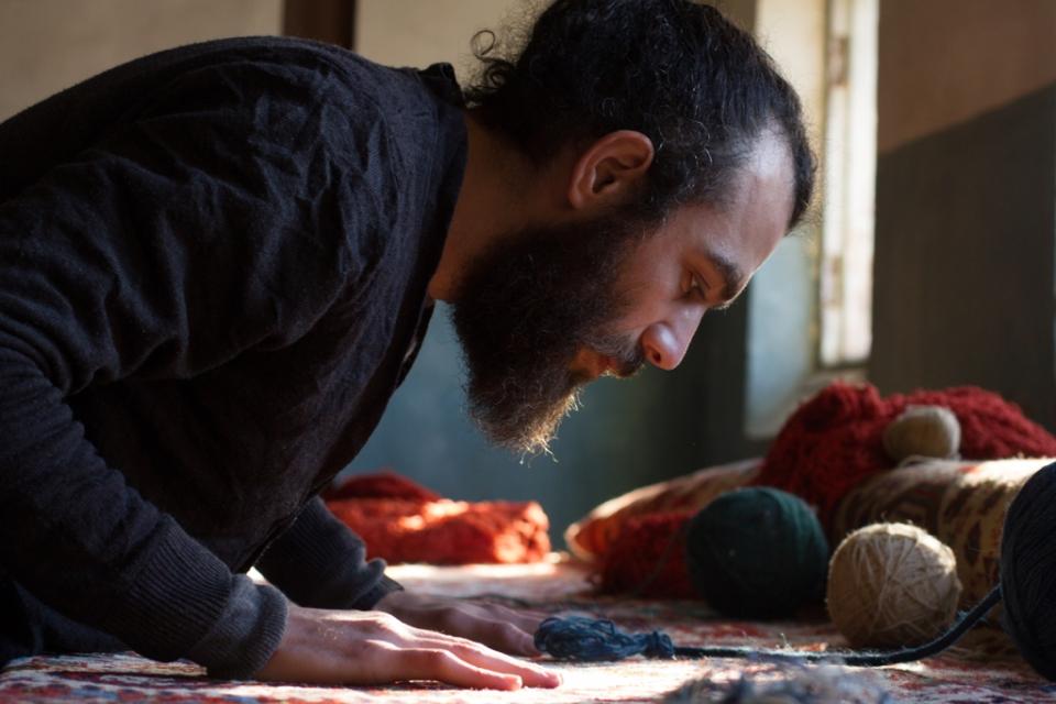 Artist bending over rug