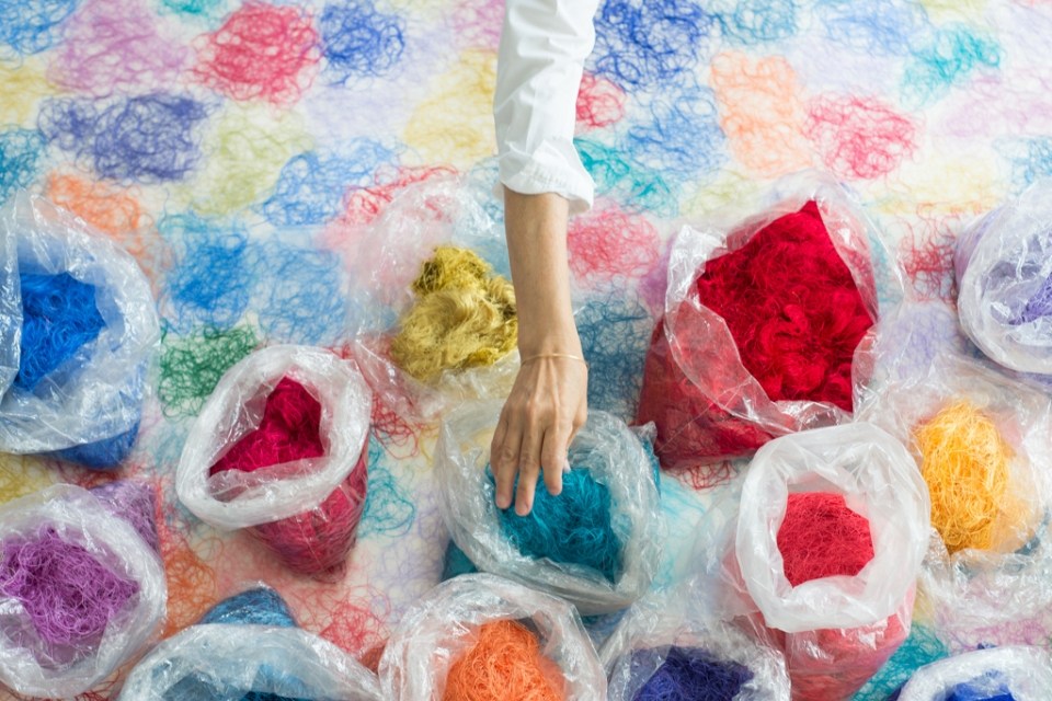 Arm reaching into bags of colorful thread