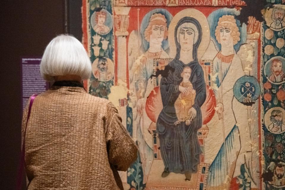 Women looks a tapestry