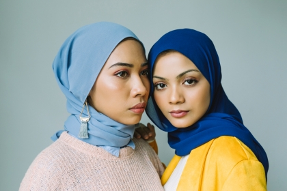 Two women standing close together wearing blue hijabs