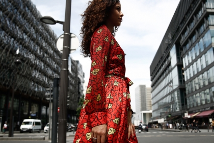 Woman in wax print dress walking in a city