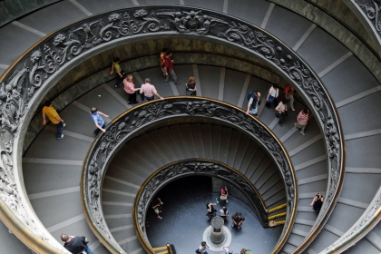 Looking down on a large, spiral staircase with people walking on the steps and around the base.