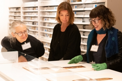 Curator shows textile fragments to two women