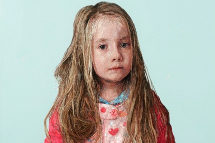 Textile portrait of a young girl with long, sandy blonde hair and a pink shirt.