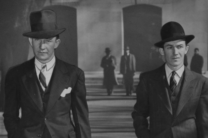 """Newspaper image of Charles """"Rags"""" Warring and Emmitt Warring walking down a street wearing suits and hats."""