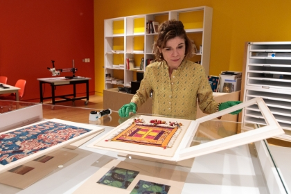 A woman stands over a glass case, opening an archival mat to look at a textile fragment.