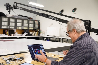Man with white hair looking at a computer screen in a photography studio with an overhead apparatus.