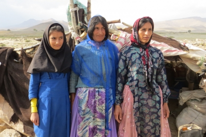 Three women wearing headcovers and long-sleeved dresses stand in front of a desert landscape.